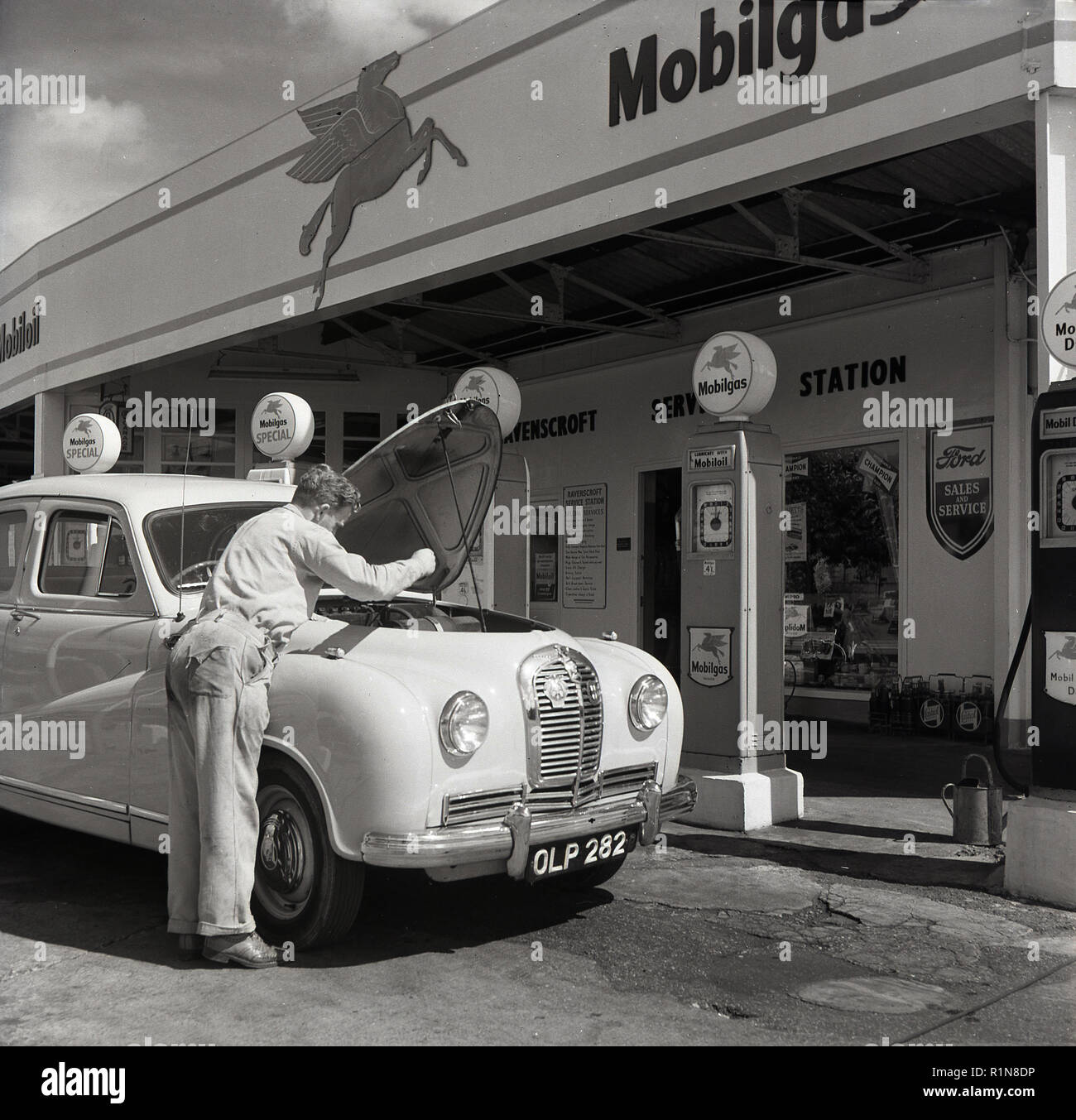 1950s, historical, the golden days of motoring, a service station sttendant checks the oil on an Austin car parked at the petrol pumps at the Mobilgas Ravenscroft Service Station, Great West Road, London, England, UK. - Stock Image