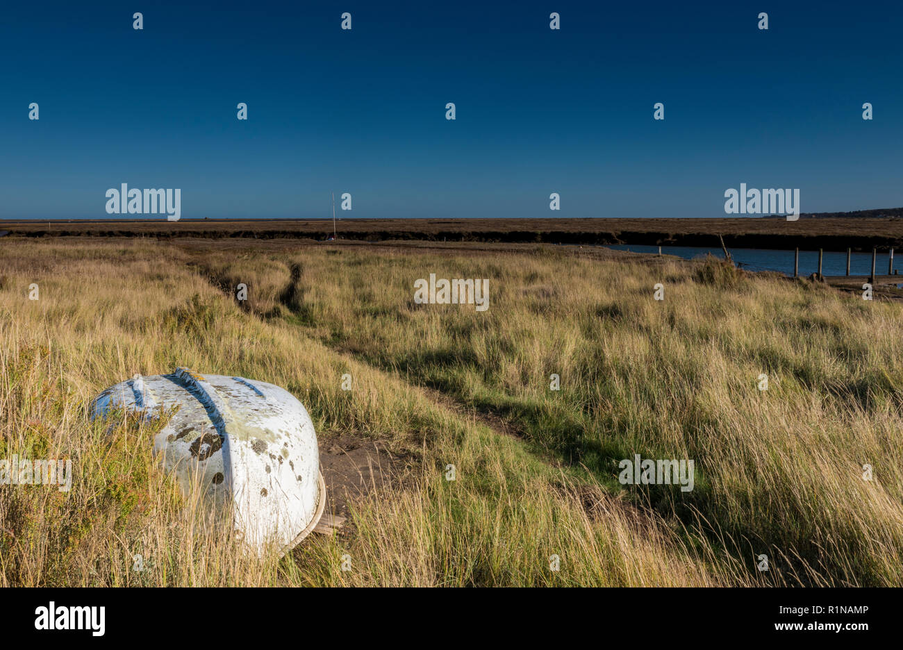 an upturned rowing boat and pathway or track across the mud flats and maram grass marshes at morston harbour or creek in Norfolk on the coast. - Stock Image