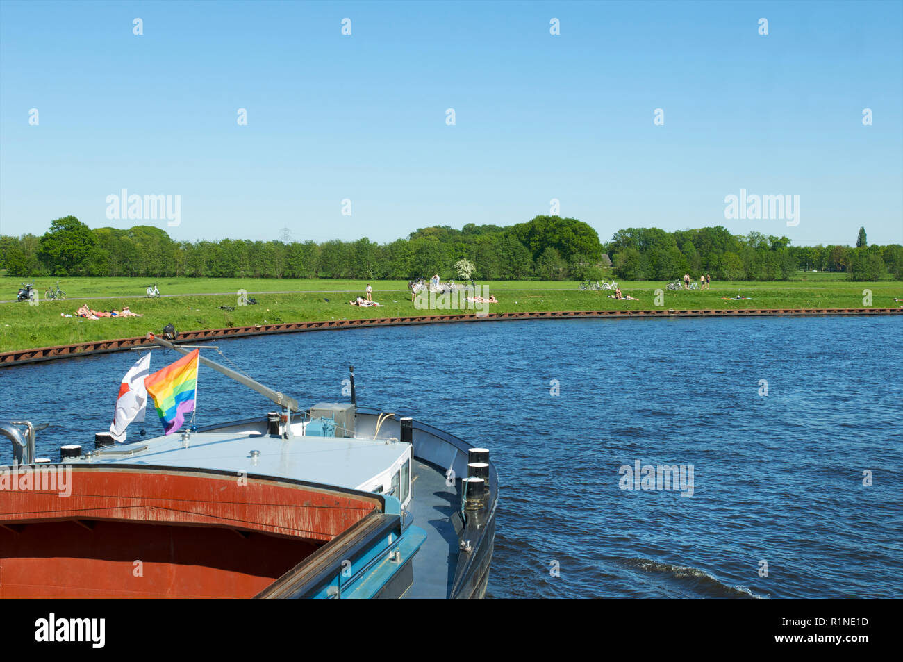 An empty freight ship with rainbow flag sailing over the canal de Eem passing people sunbathing an recreating at the water, the Netherlands - Stock Image