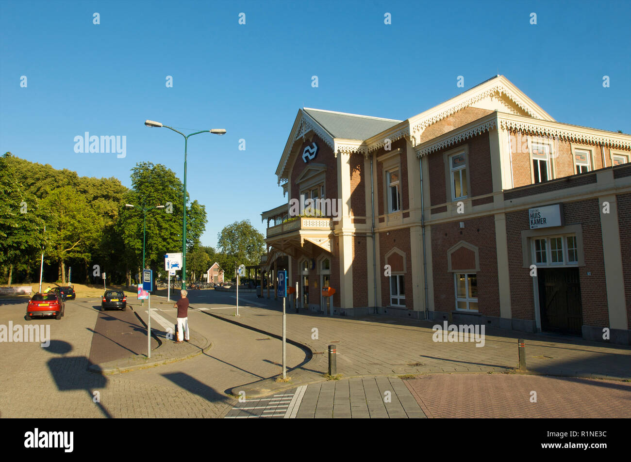 The front side of the historic railway station in Baarn with a kiss and ride area used for the Dutch Royal family, the Netherlands - Stock Image