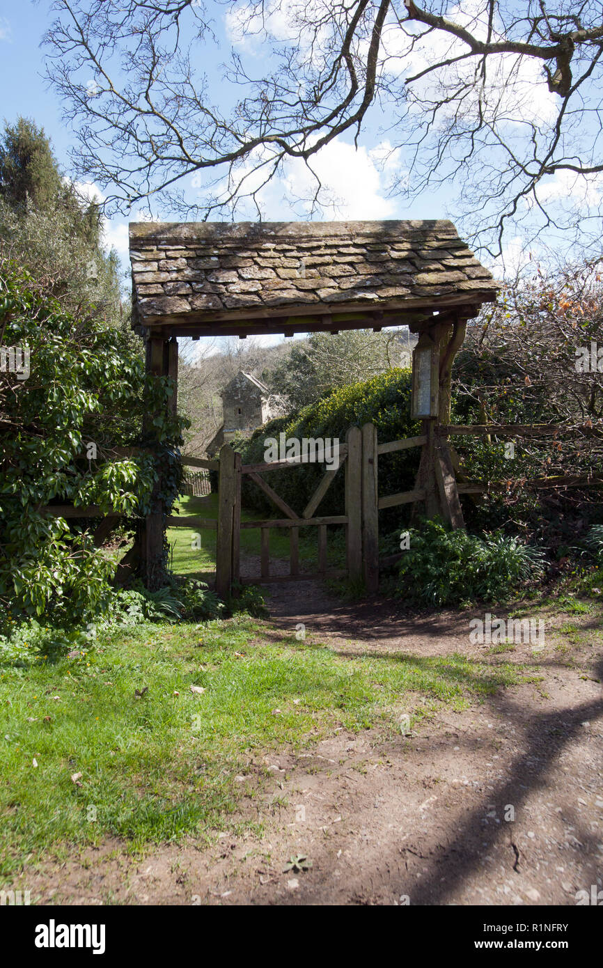 The picturesque old lychgate frames the tiny old Saxon church in spring sunshine at Duntisbourne Rouse in the Cotswolds, Gloucestershire, UK - Stock Image