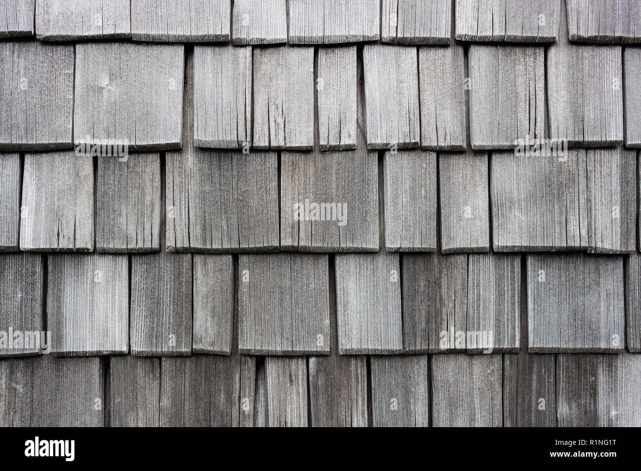 Wood shingle wall siding made of larch. Old, discolored and worn by weather shingles. Traditional austrian house siding. - Stock Image