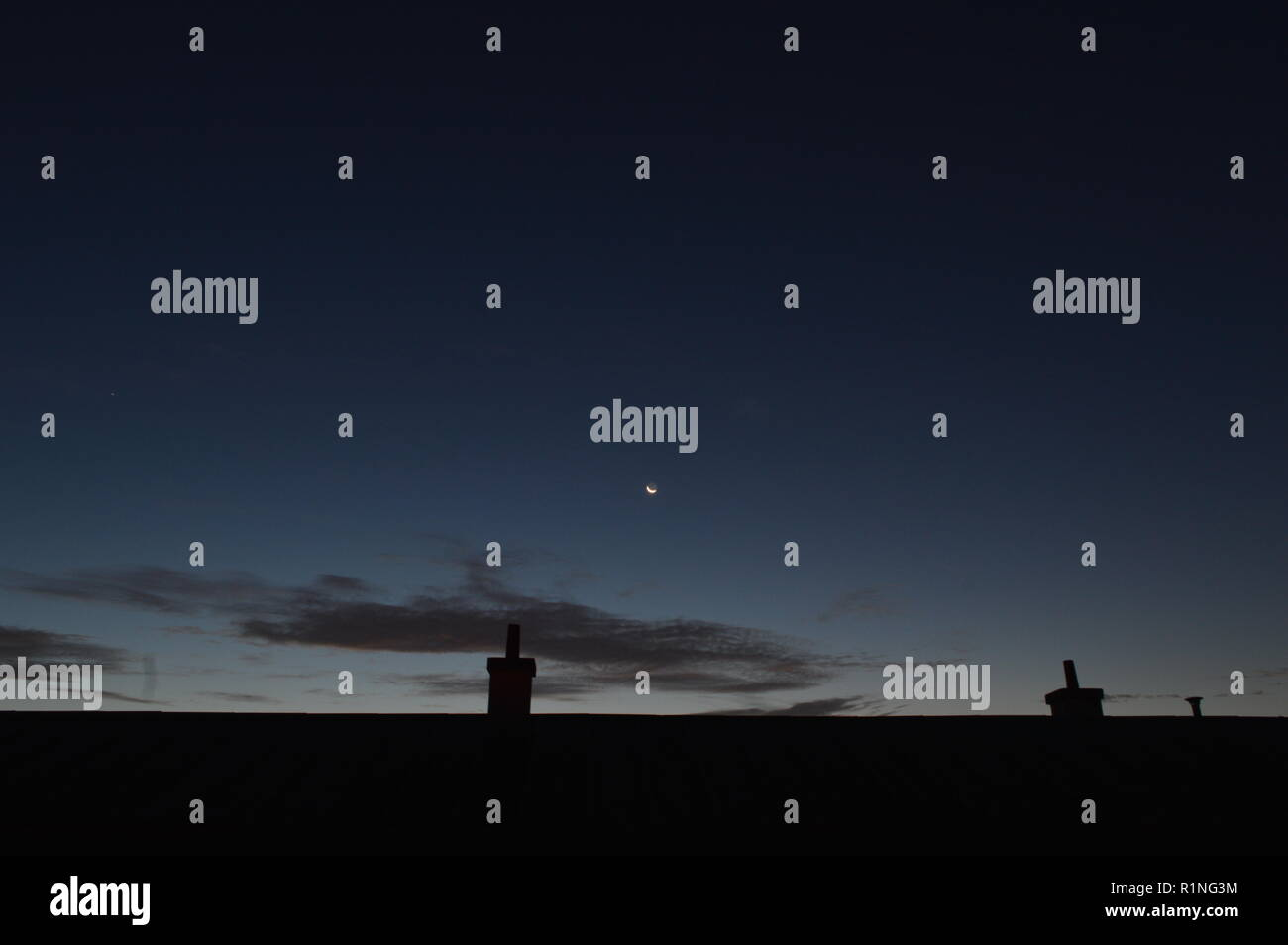 moon over a roof on early morning - Stock Image