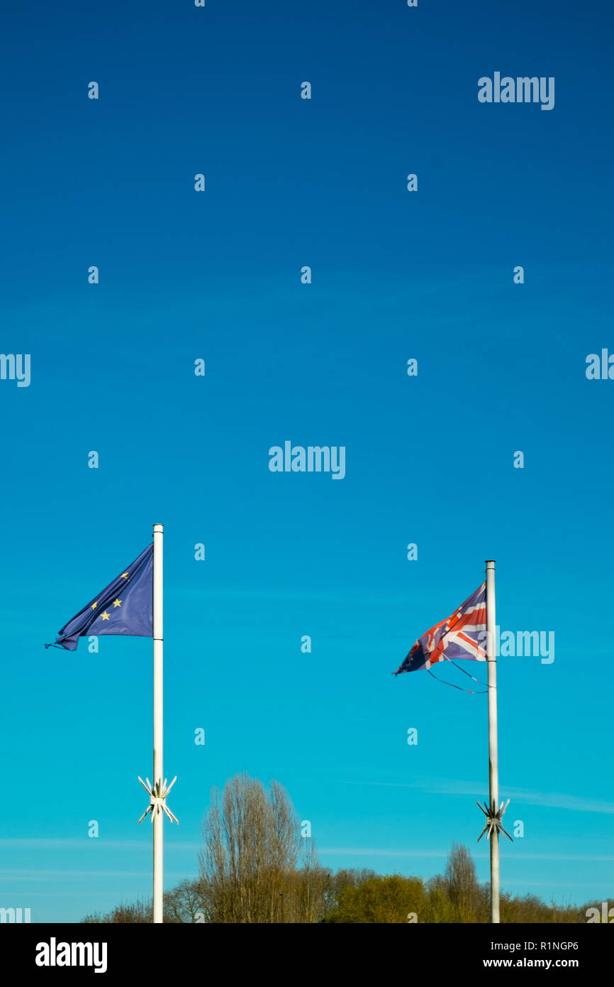 Brexit. Frayed and faded flags of the United Kingdom and the European Union flap in a blue sky Stock Photo