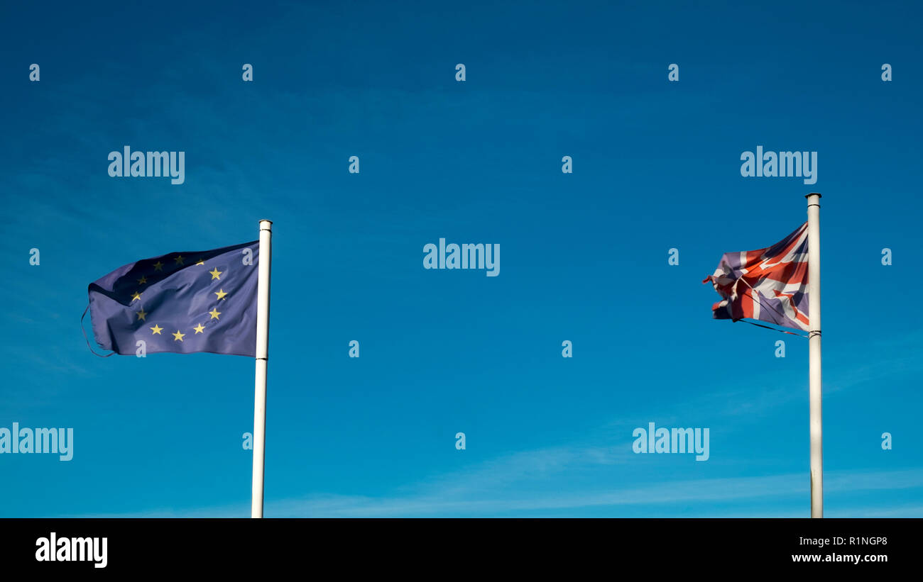 Brexit. Frayed and faded flags of the United Kingdom and the European Union flap in a blue sky - Stock Image