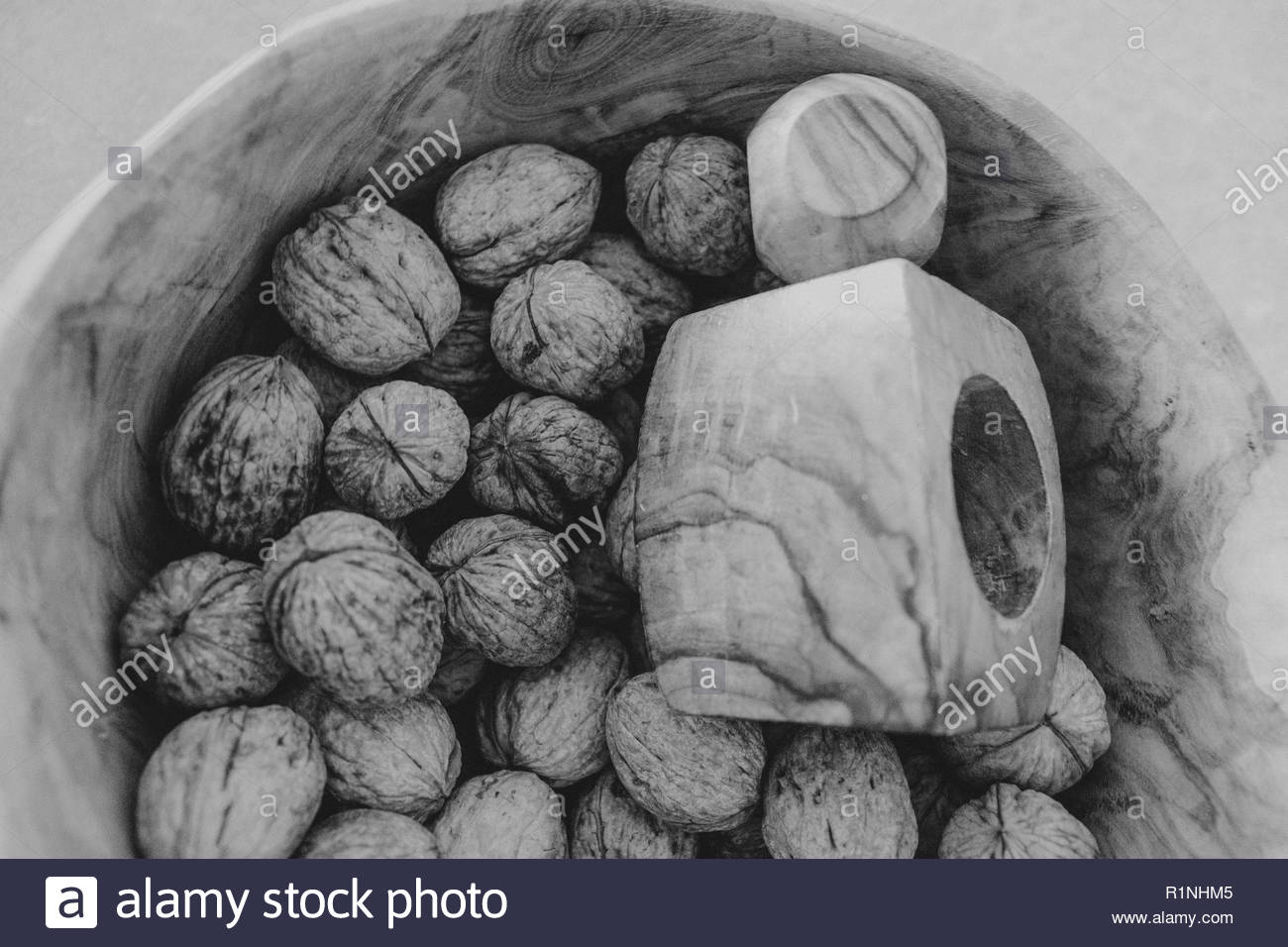 walnuts with wooden opener in an artisan bowl - Stock Image