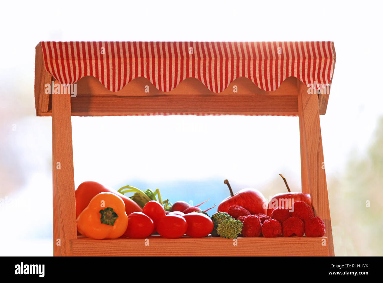 miniature market stall with vegetables and fruits, blurred background - Stock Image