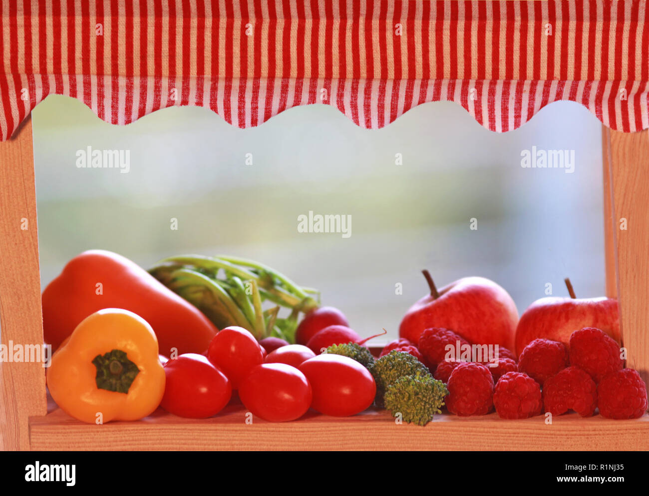 miniature market stall with various fruits and vegetables, close-up, background with copy space - Stock Image