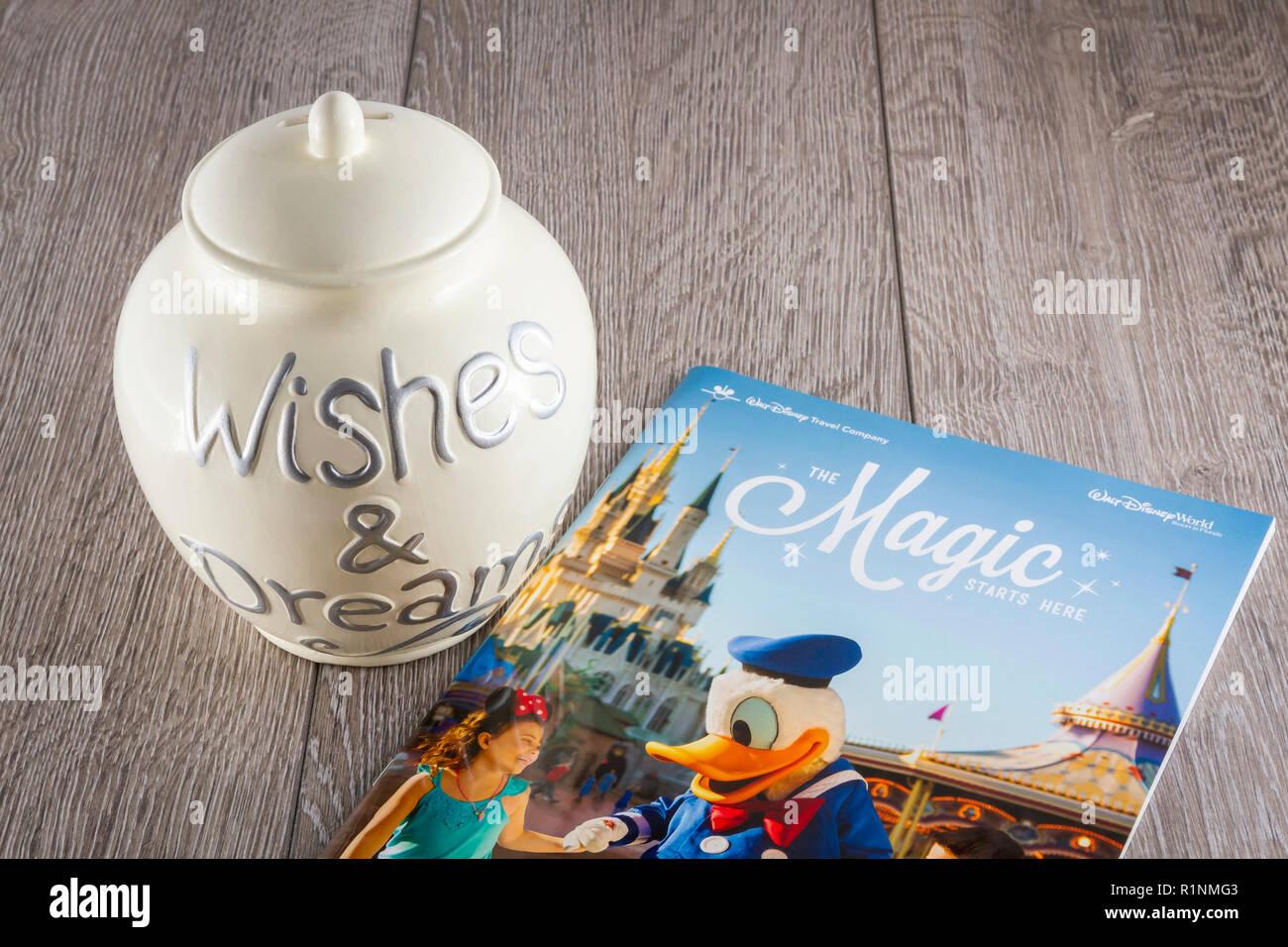 Savings Jar with a Walt Disney World Travel Brochure - Stock Image