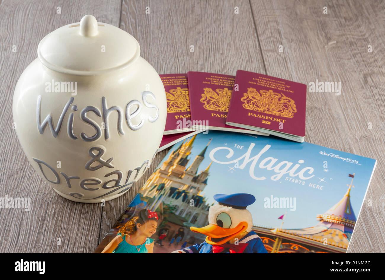 British passports and a savings jar with a Disney World Travel Brochure - Stock Image