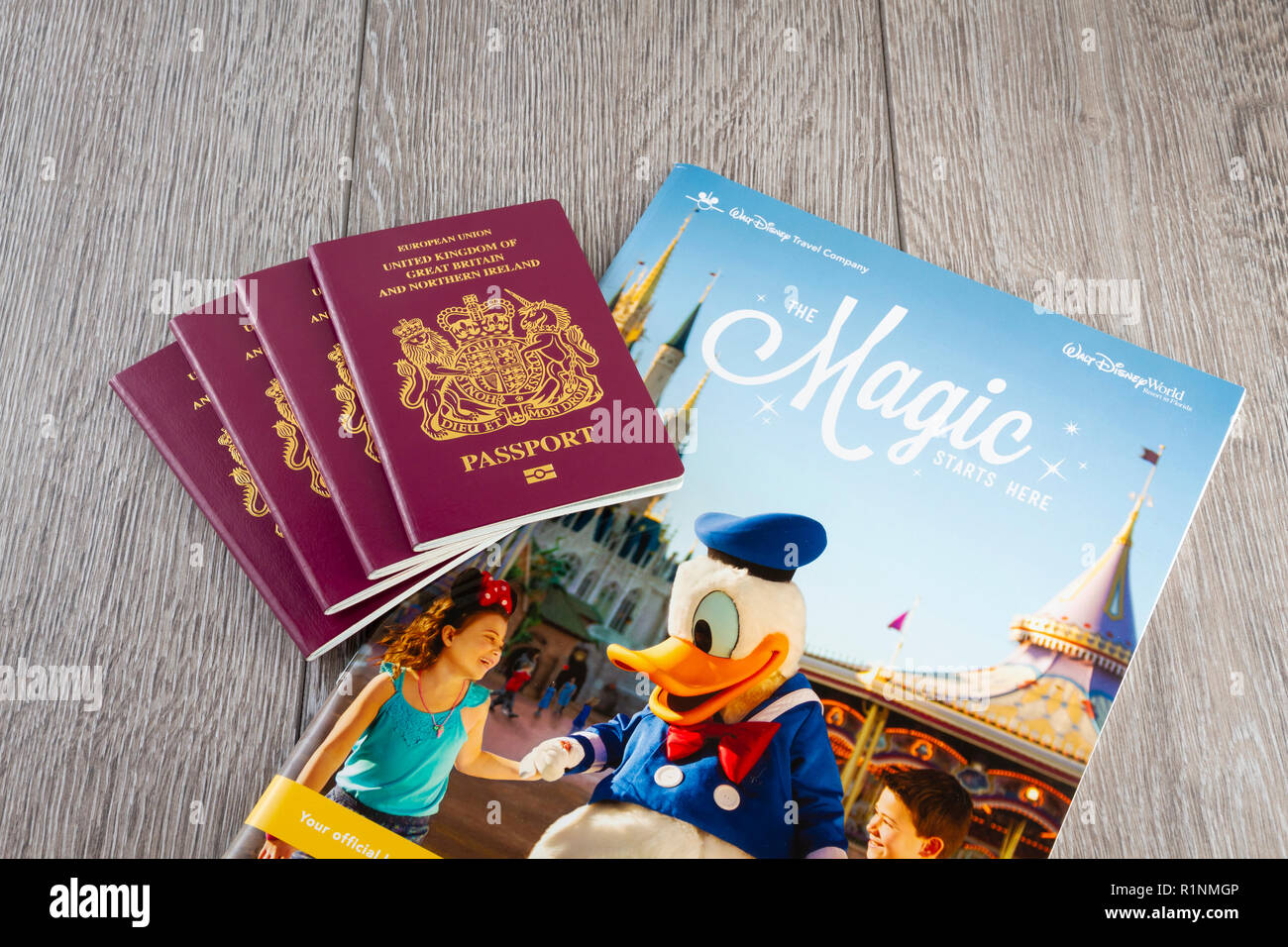 Four passports with a Disney World Travel Brochure - Stock Image