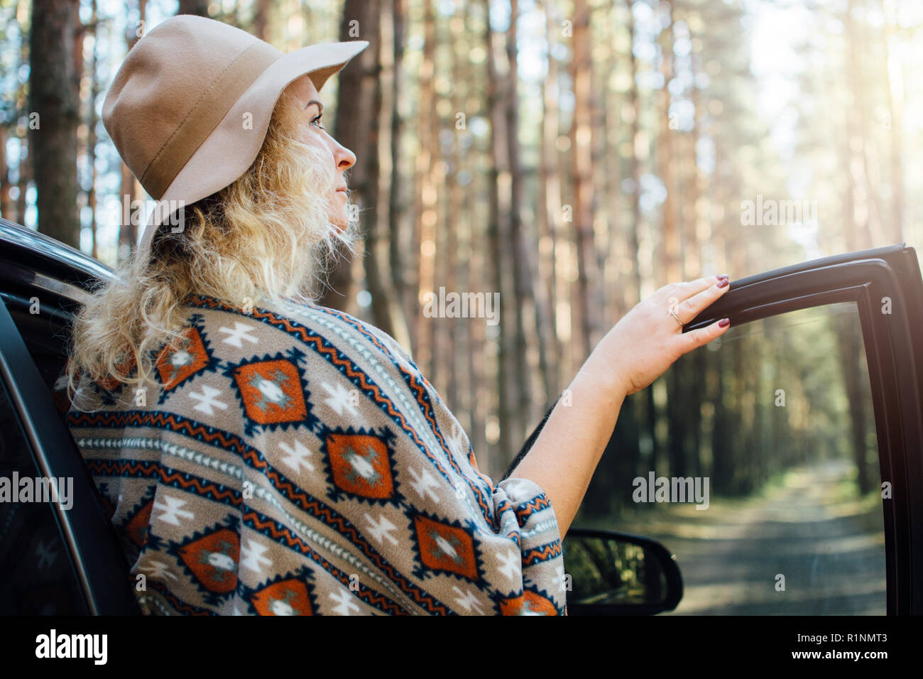 Woman in wide-brimmed felt hat and authentic poncho standing opening car door in the pine tree forest. - Stock Image