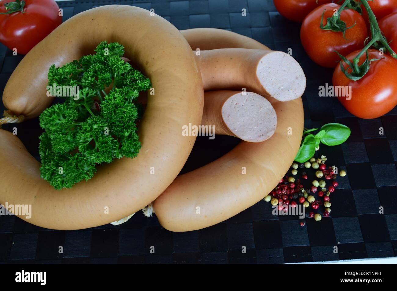 Lyoner is a Sausage delicatessen on a black placemat.                 Lyoner ist ein Wurst-Delikatessen auf einem schwarzen Tischset. - Stock Image
