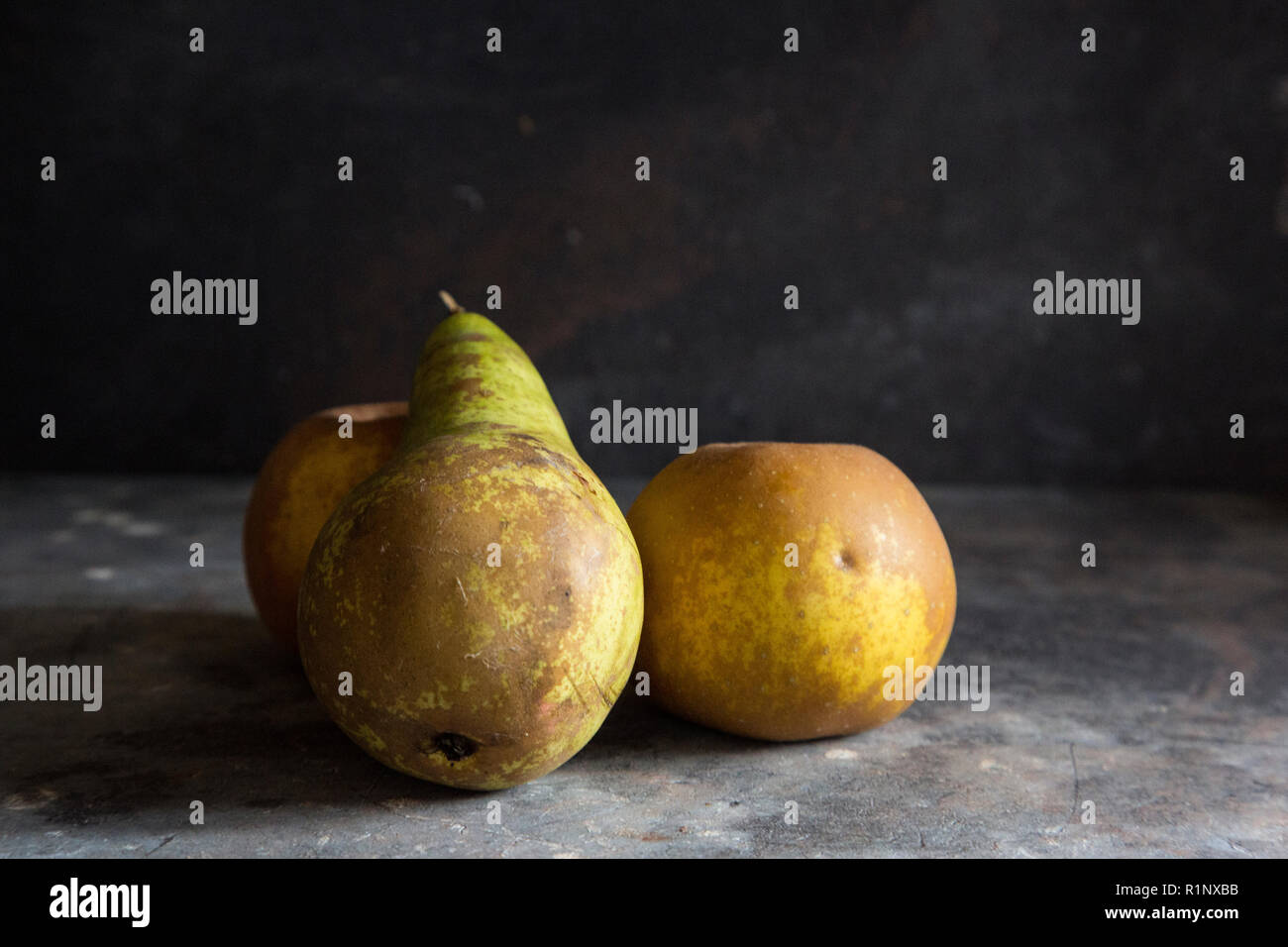 a pear and two russett apples on a grey textured background with darker lighting creating a moody dark feel to the image Stock Photo