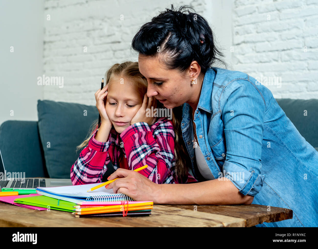 Patience mum with daughter unable to concentrate whilst doing homework sitting on sofa at home in learning difficulties homework parenting and educati - Stock Image