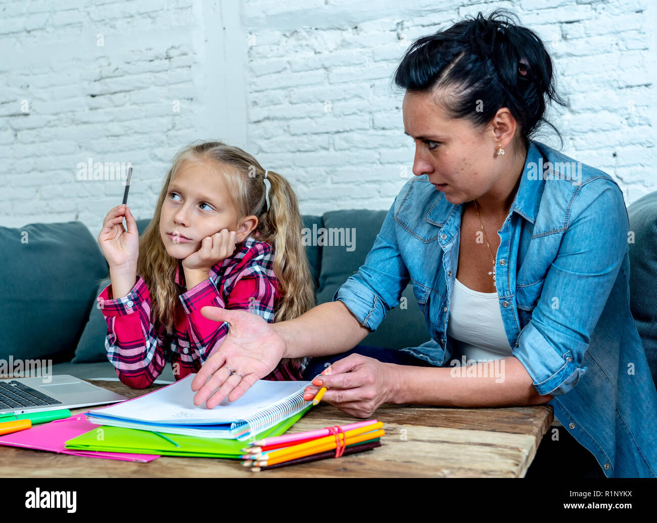 Mother becoming frustrated with daughter whilst doing homework sitting on sofa At home in learning difficulties homework parenting and education conce - Stock Image