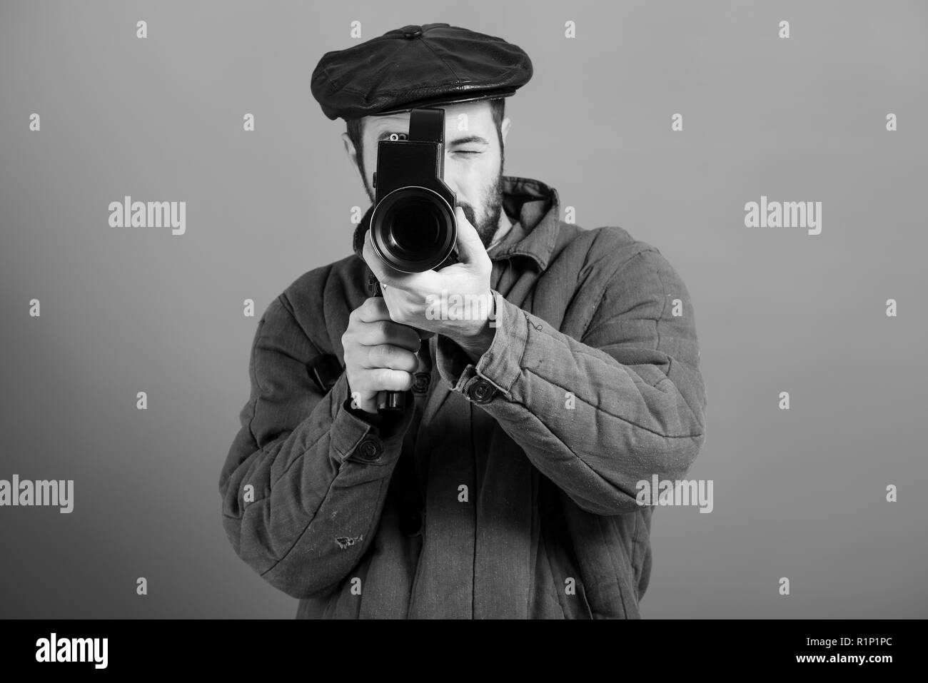 Idea- cinema industry. Cameraman with retro camera in his hands, studio shot, monochrome effect. Bearded man in old-fashioned dress - Stock Image