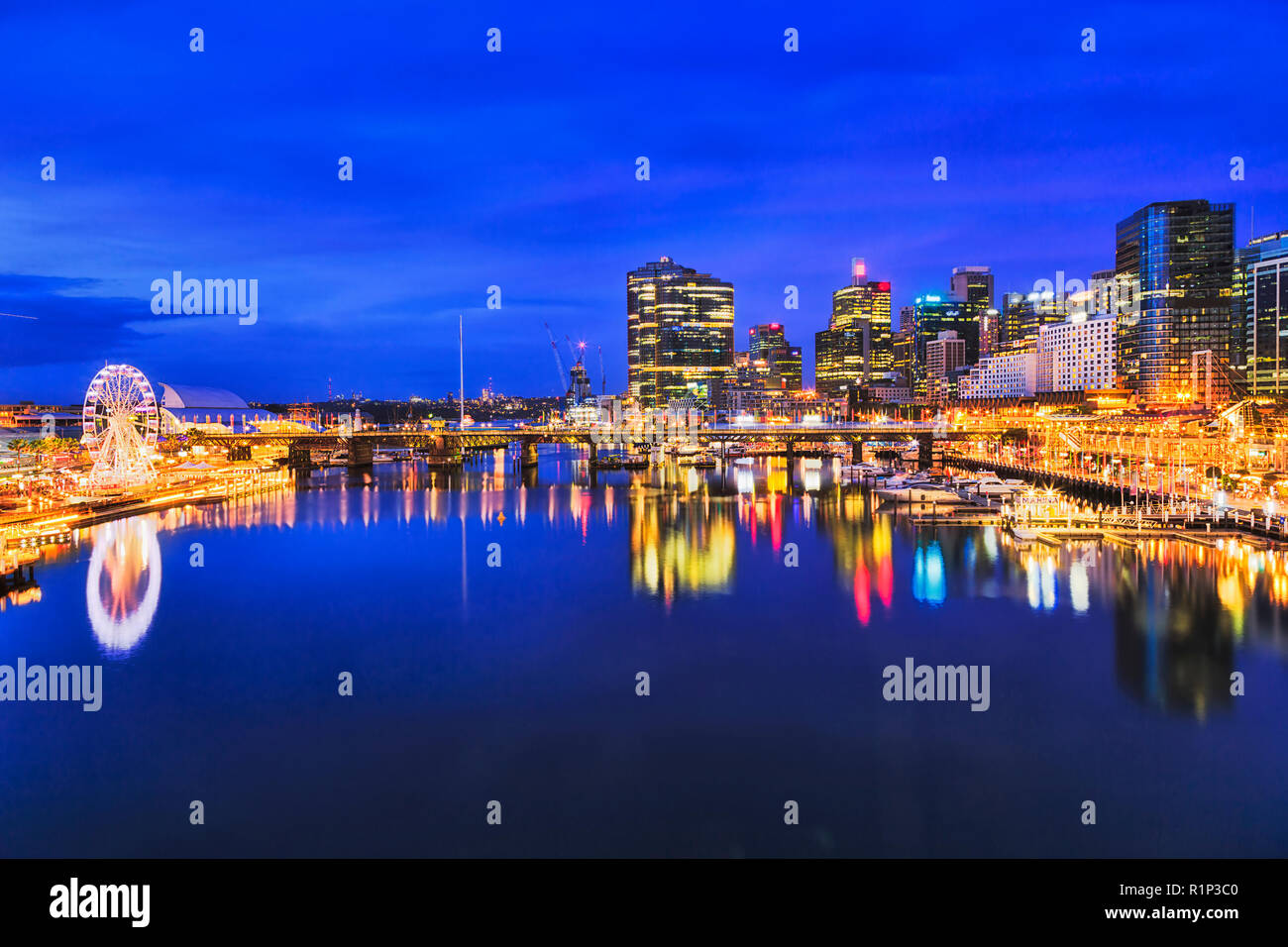 Blue dark sunset in Darling harbour entertainment district of Sydney CBD when bright illumination lights reflect in still waters of Cockle bay. - Stock Image