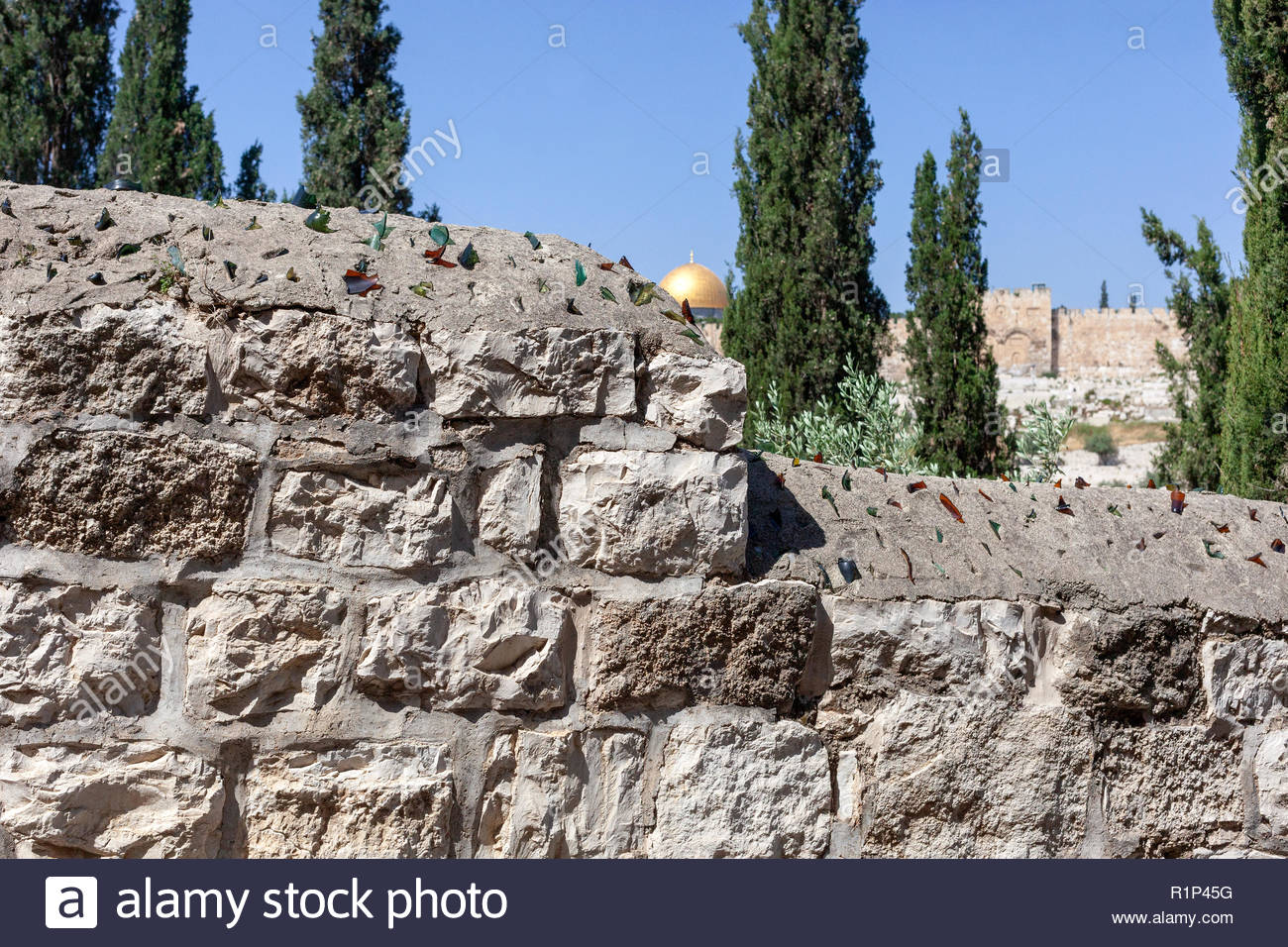 Glass Embedded in a Protective Stone Wall; Dome of the Rock and the Eastern Wall of Jerusalem in the background - Stock Image