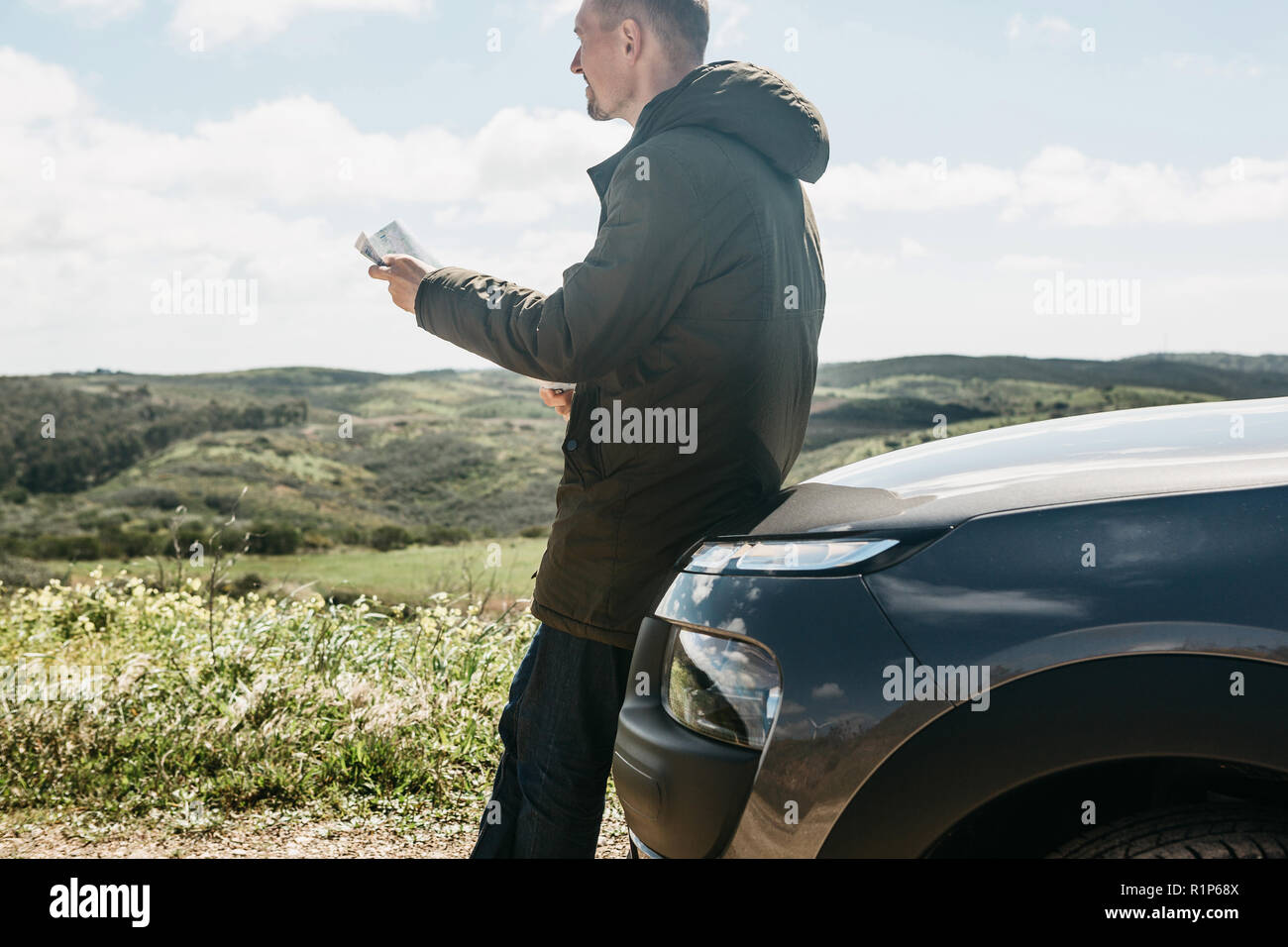 A tourist man next to the car looks at the map of the area for further travel. - Stock Image