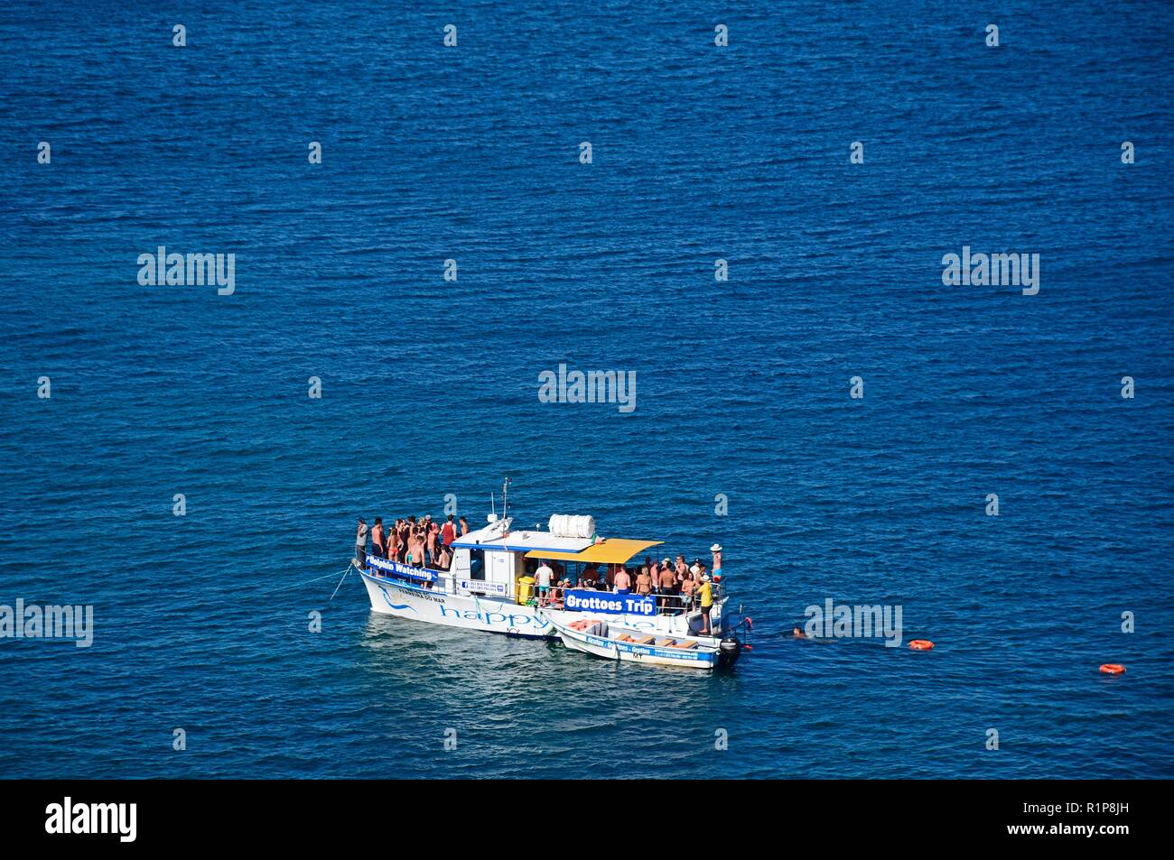 Elevated view tourists on a dolphin watching boat in the bay, Ponta da Piedade, Lagos, Algarve, Portugal, Europe. - Stock Image