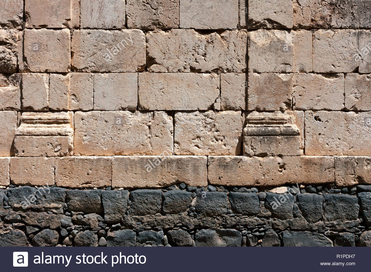 Synagogue wall at Capernaum; calcareous stone wall built on a basalt stone base - Stock Image
