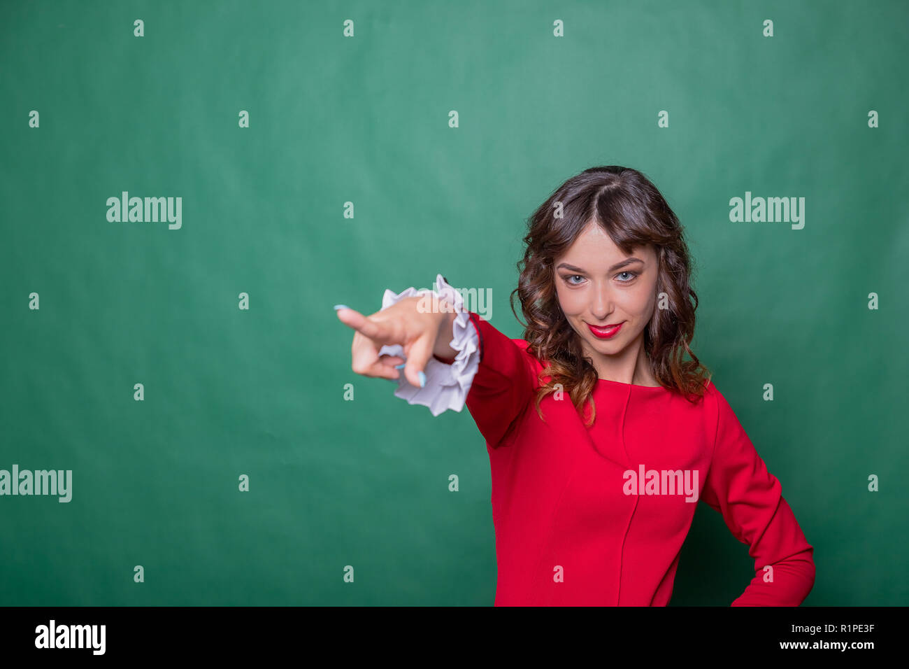 Image of cheerful woman with long brown hair winking and showing index finger aside meaning hey you isolated over green background.Emotional expressing woman in red dress, red lips and dark curly hairstyle.Copy space - Stock Image