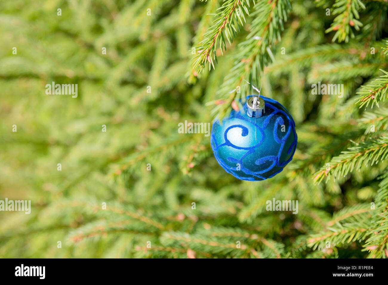 Beautiful blue color christmas decorations hanging on christmas tree with shiny glare.Christmas tree branch with snow and blue ornament. New year greeting background. Copy space.Family holiday.Abstract christmas lights Stock Photo