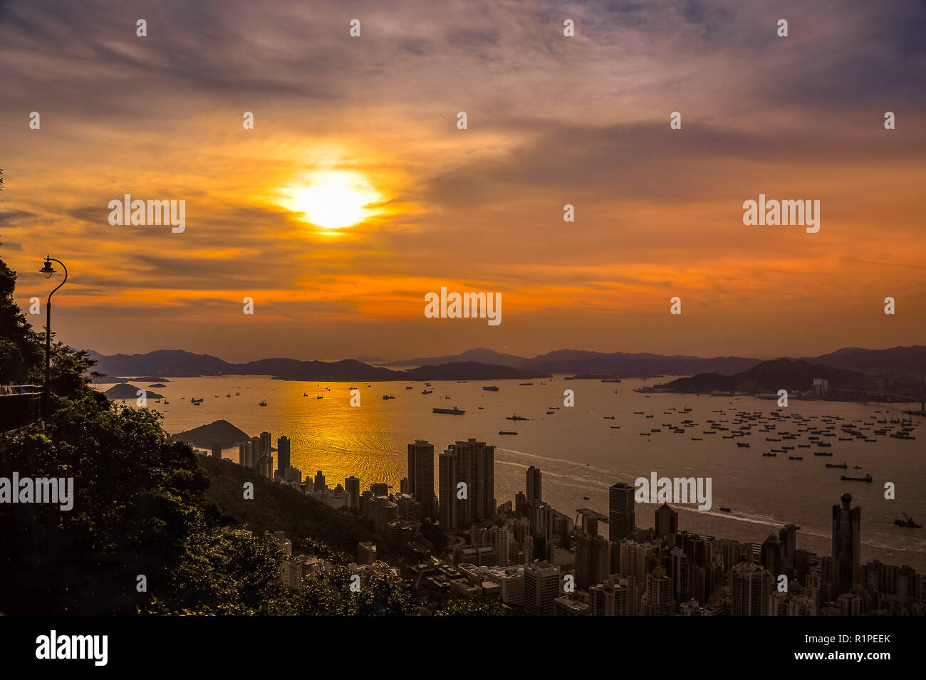 Sunset over Hong Kong harbour from Lugard Lookout, Victoria Peak. Dazzling orange sun sets over distant islands with city highrises in the foreground. - Stock Image