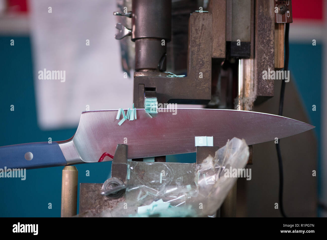 Knife blade making test cut with paper on machinery, manufacturing - Stock Image