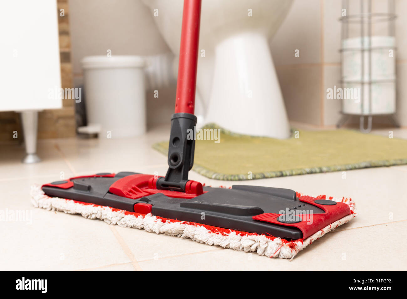 Microfiber mop on white bathroom floor tiles as cleaning concept - Stock Image