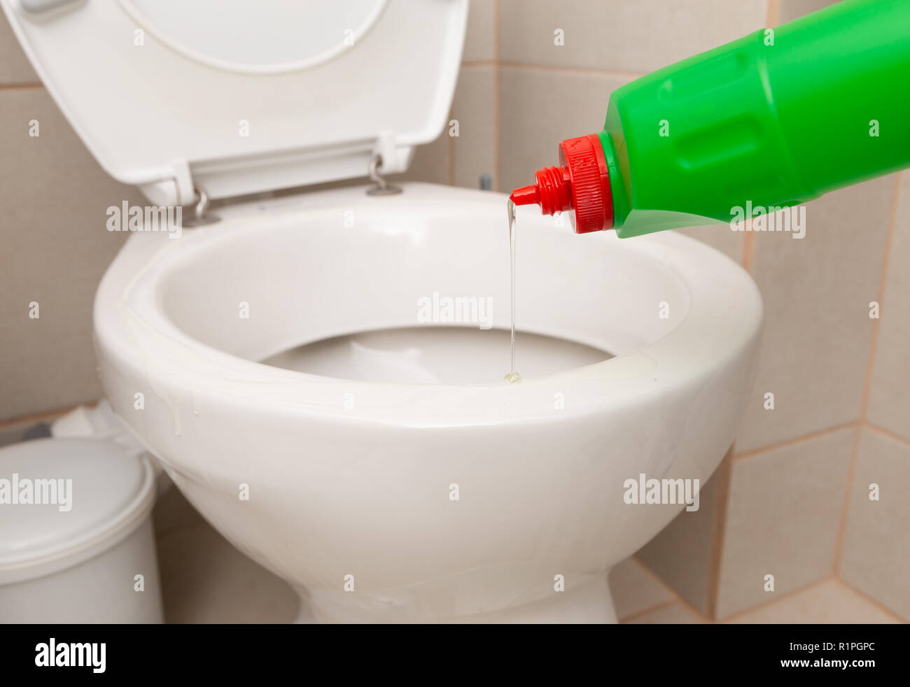 Disinfectant from green bottle being poured in white porcelain toilet bowl as hygiene concept - Stock Image