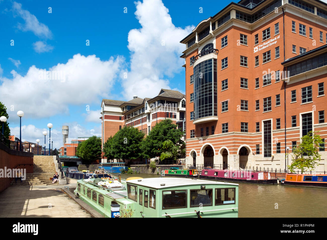 Bristol, UK - 4th August 2016: Moored canal boats and modern office blocks along The Floating Harbour and Temple Back (Temple Quay) regeneration business area in central Bristol City, UK. Workers leave their workplaces during a sunny summertime lunch break. - Stock Image