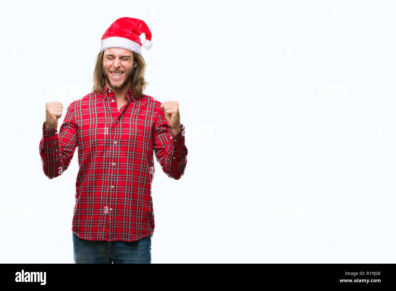 Young handsome man with long hair wearing santa claus hat over isolated background very happy and excited doing winner gesture with arms raised, smili - Stock Image