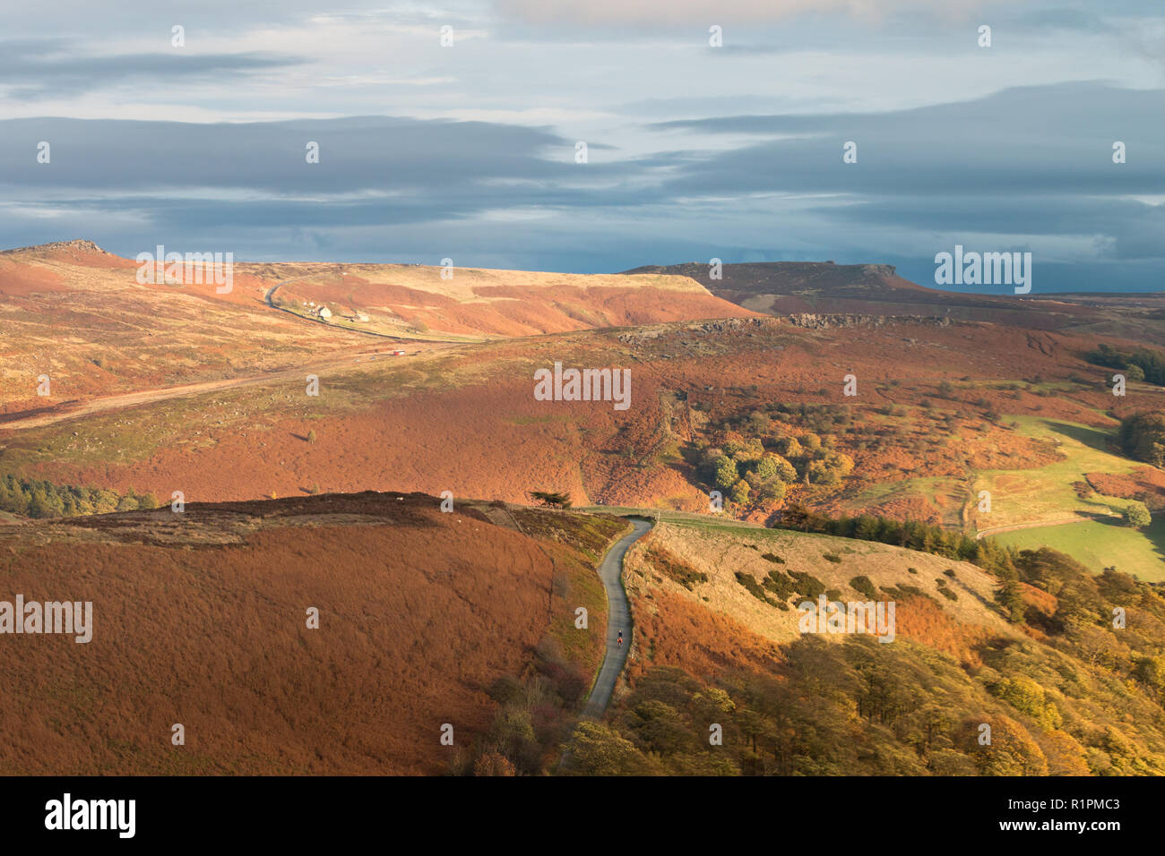 Two cyclists coast down the country lane with Dark Peak Moors in the background. - Stock Image