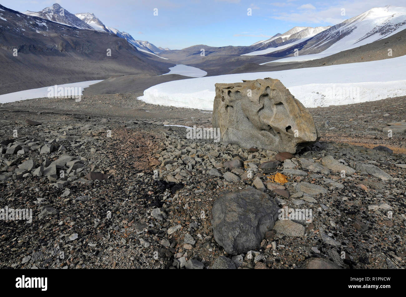 Taylor Valley, McMurdo Dry Valleys, Antarctica looking down valley towards ice-covered Lake Bonney with a large ventifact in foreground - Stock Image