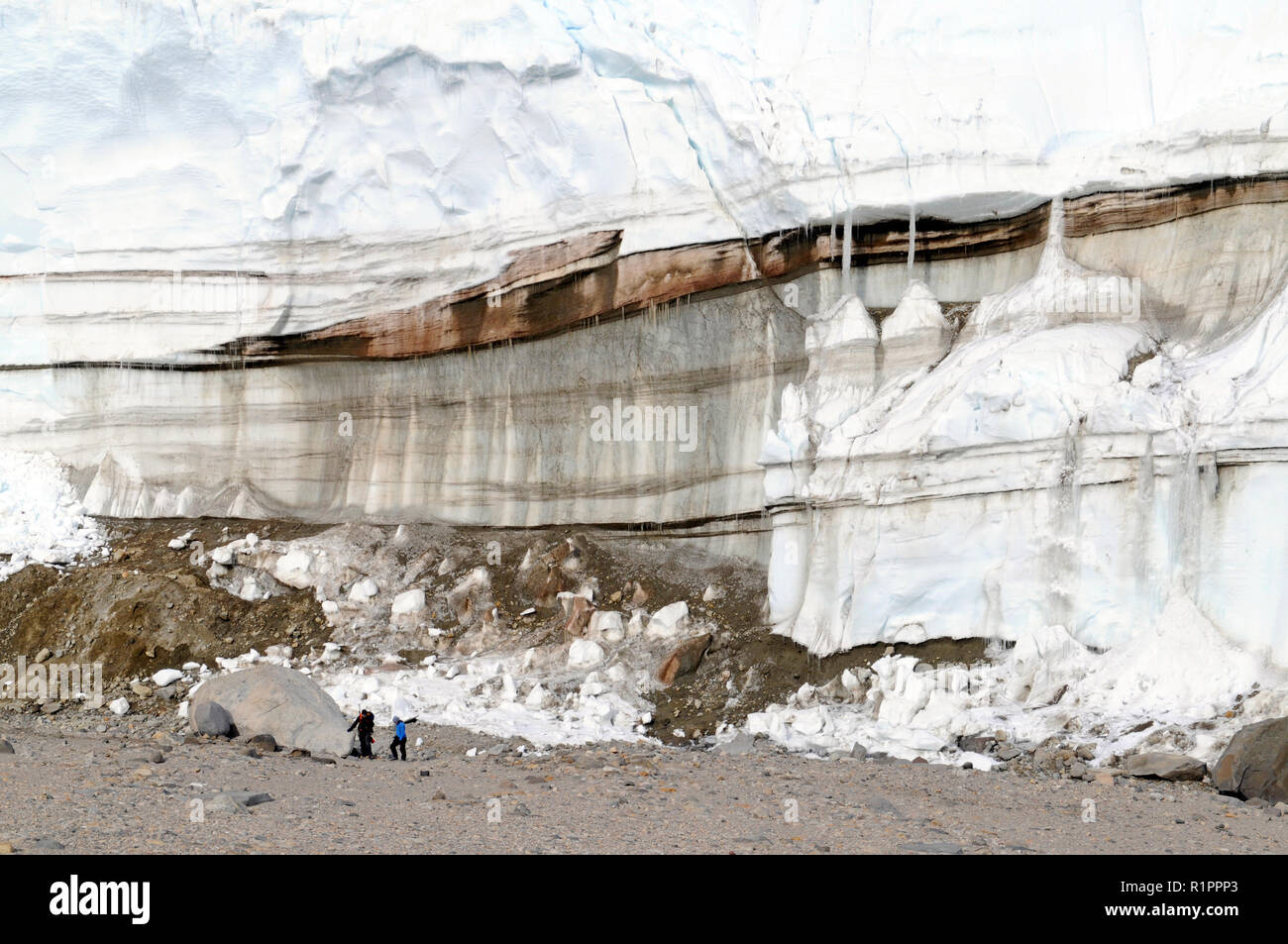 Layers of red color from iron deposits within glacier associated with Blood Falls at Taylor Valley, McMurdo Dry Valleys, Antarctica with 2 people - Stock Image