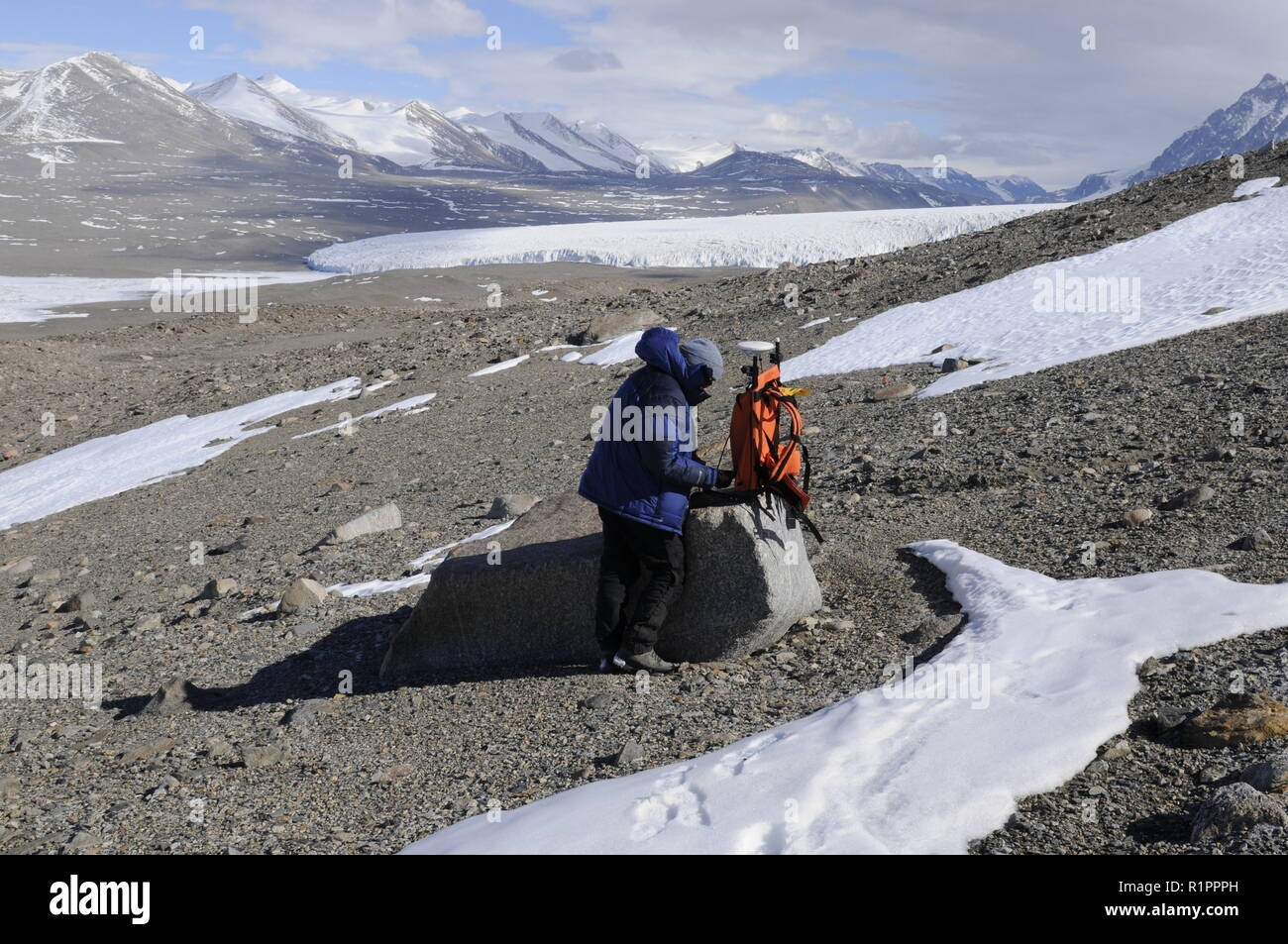Scientist recording GPS data in Taylor Valley, McMurdo Dry Valleys, Antarctica, with Lake Fryxell and Canada Glacier in background - Stock Image