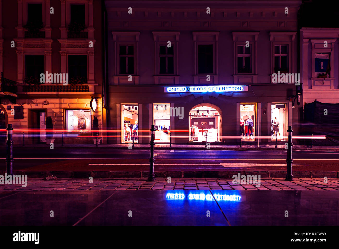 Brasov, ROMANIA - October 21, 2018: United Colors of Benetton store across the Old Town Square of Brasov. Night scene with neon lights and light trail - Stock Image