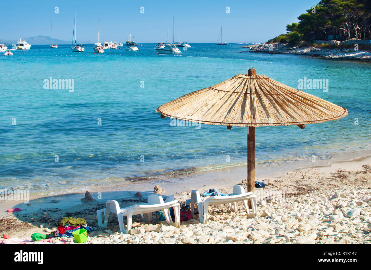 One yellow straw umbrella and two chairs on the pebble sandy beach. Many yachts in the azure blue sea lagoon in a bay near the coast of an island. Blu - Stock Image