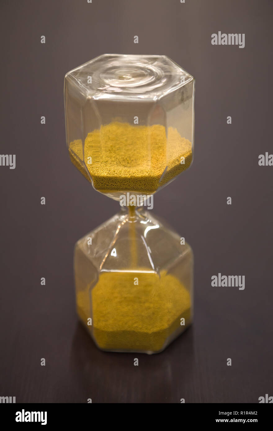 Hourglass on rustic wooden table. Time running out or deadline concept. Closeup - Stock Image