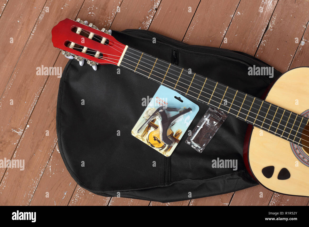 Musical instrument - Classic Guitar, case, capo, key, picks set wood background. Stock Photo