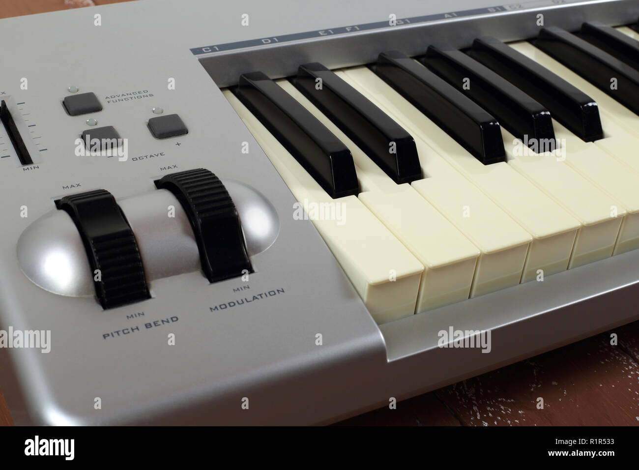 Musical instrument - Sloseup fragment MIDI piano 61 key keyboard on a wooden background - Stock Image