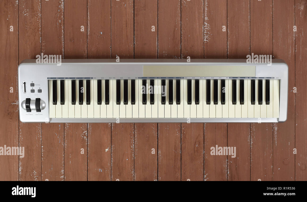 Musical instrument - Sloseup MIDI piano 61 key keyboard on a wooden background - Stock Image