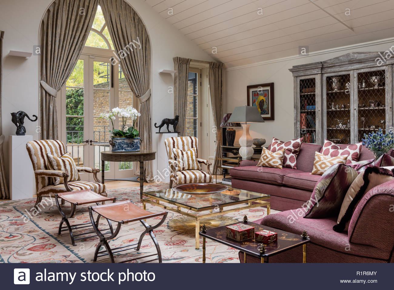 Country style living room with tieback curtains - Stock Image