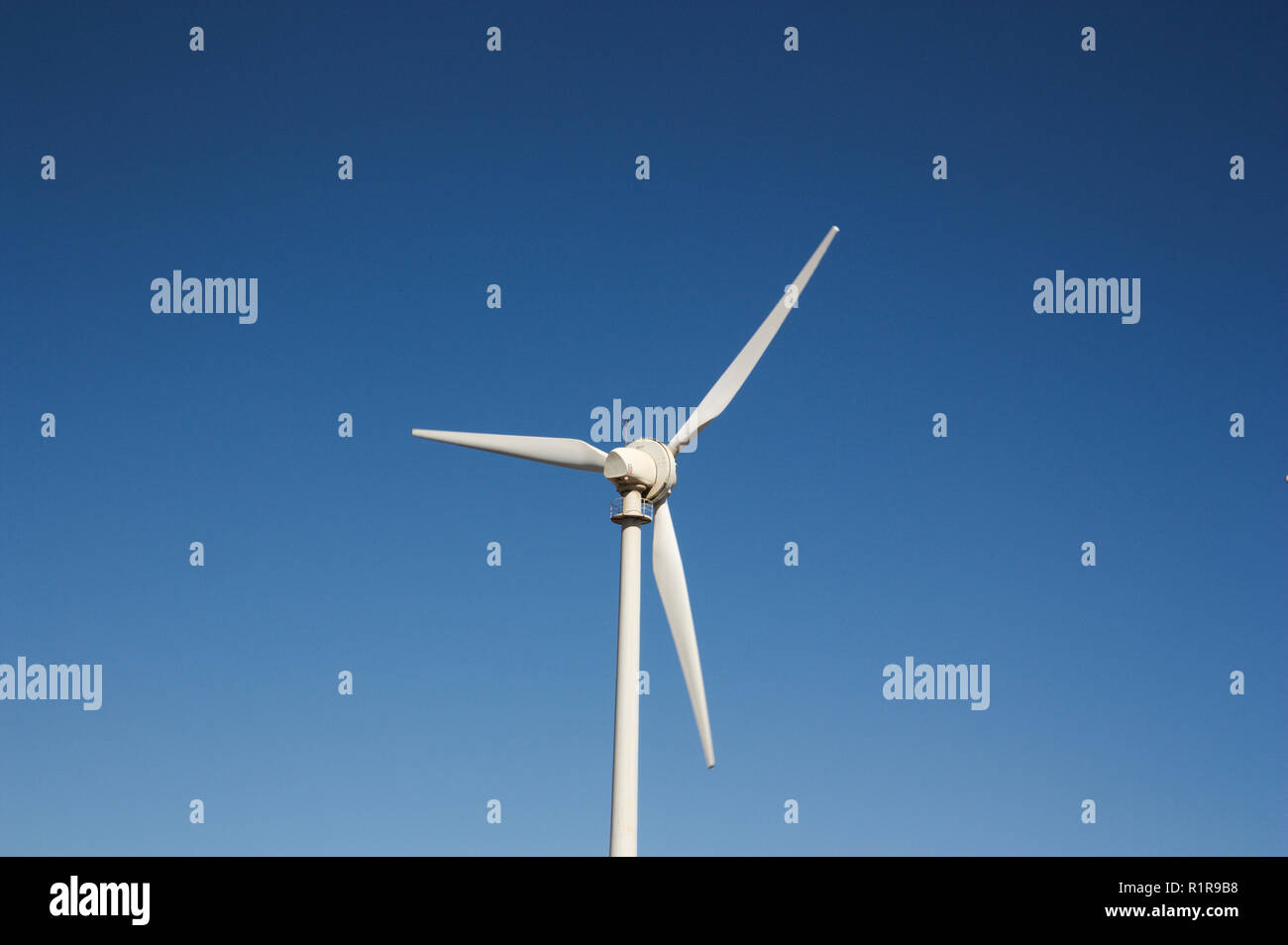 A wind turbine that rotates with the force of the wind isolated with blue sky background - Stock Image