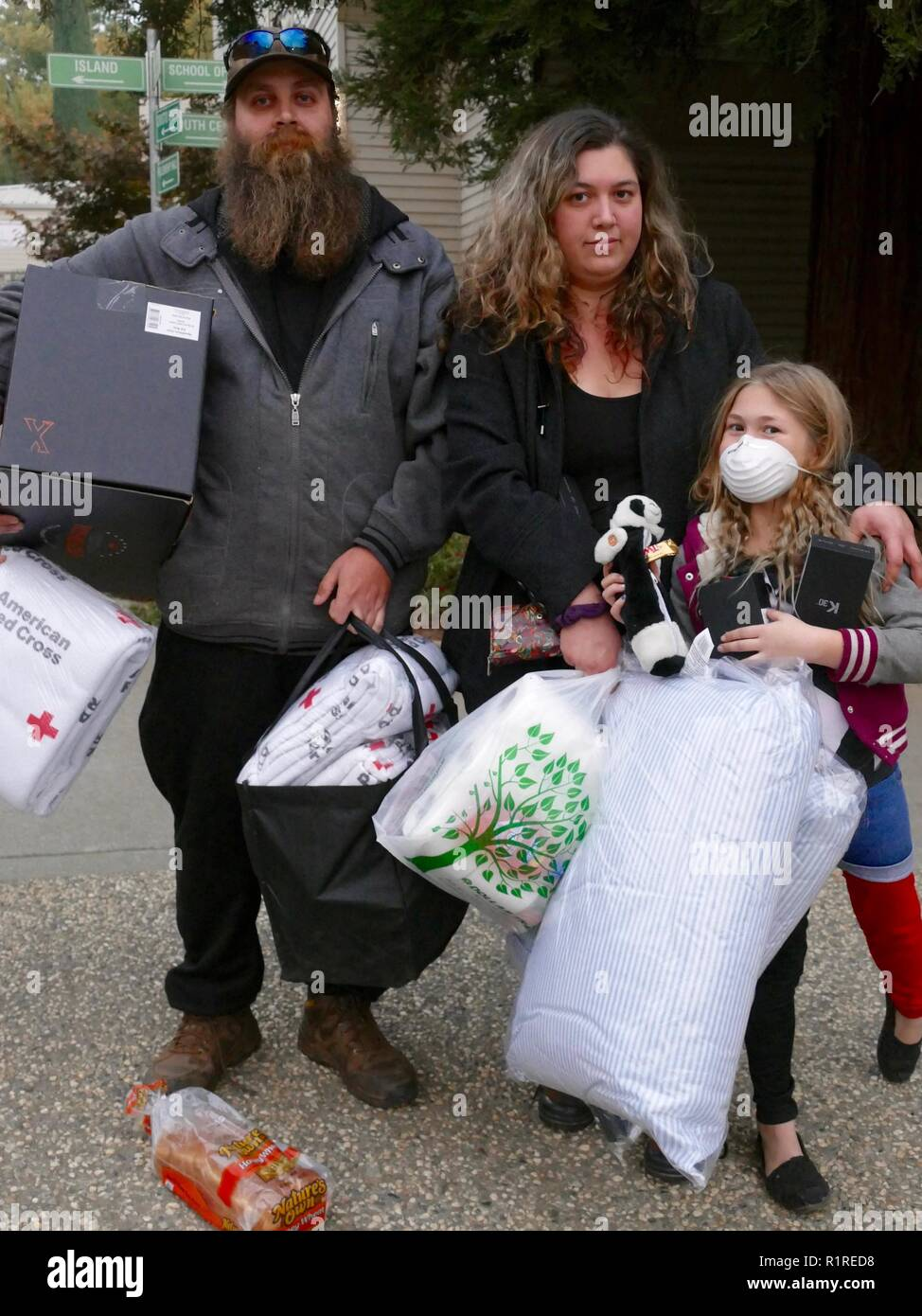 Paradise, USA. 13th Nov, 2018. Sierra Strongheart, her friend Jason Woods and daughter Brooke, a family from Paradise, stocked up on donations after the forest fire, the so-called 'camp' fire, lost their belongings. (to dpa 'Paradise as hell on earth - 'Will create a new church' of 14.11.2018) Credit: Barbara Munker/dpa/Alamy Live News - Stock Image