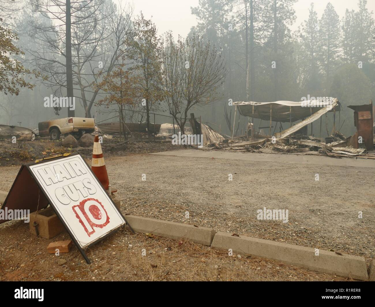 Paradise, USA. 13th Nov, 2018. '$10 haircuts' is on a sign by the side of the road in front of a burnt-out hair salon. Paradise became a ghost town after the forest fire, the so-called 'camp' fire. Only fire engines and fire engines drive through the spooky landscape. Residents are not allowed to return for the time being. (to dpa 'Paradise as hell on earth - 'Will create a new church' of 14.11.2018) Credit: Barbara Munker/dpa/Alamy Live News - Stock Image