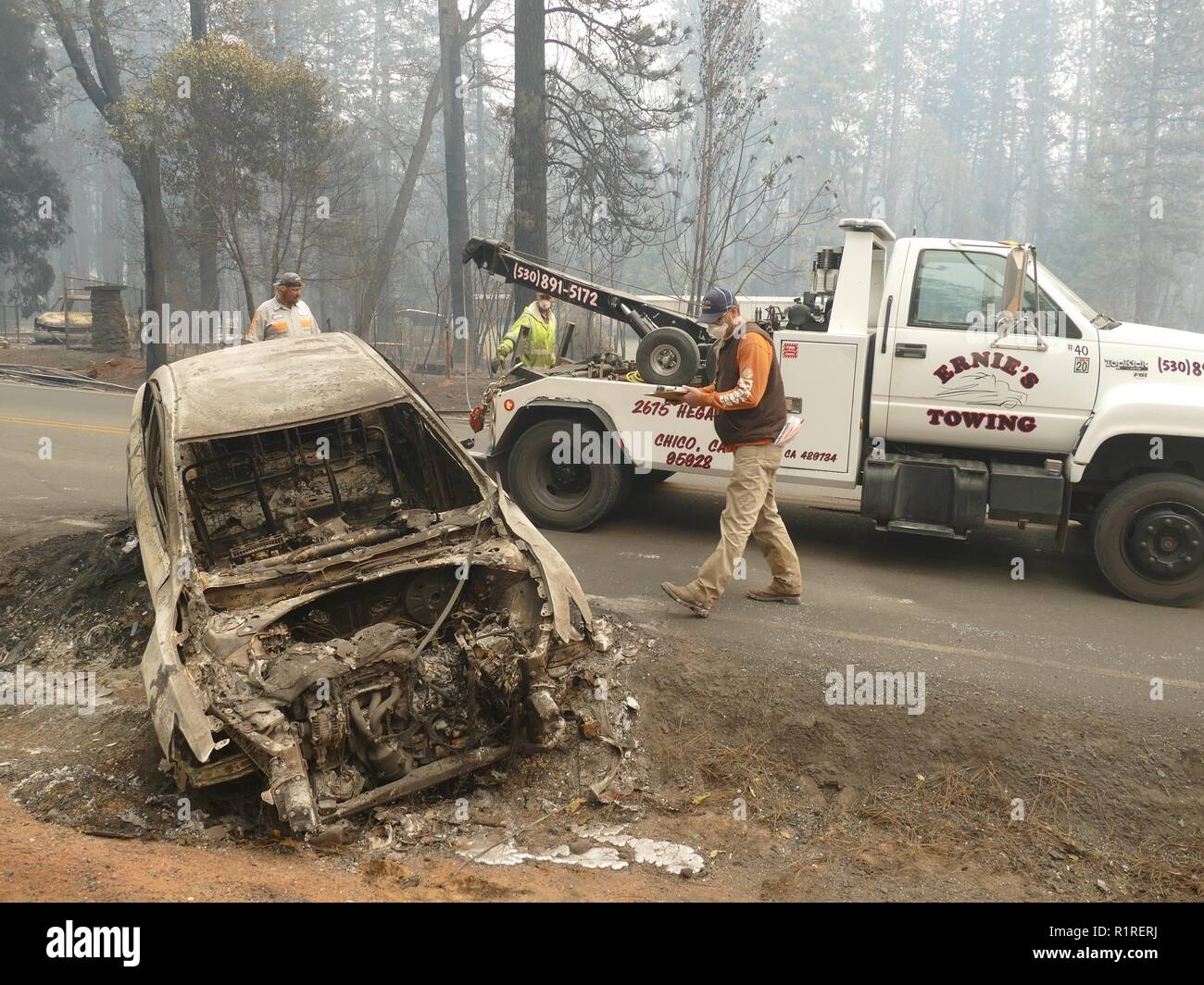 Paradise, USA. 13th Nov, 2018. Matt Hyatt of Highway Patrol transports burnt-out cars from the roadside after the forest fire, the so-called 'camp' fire. Paradise has become a ghost town. Only fire engines and fire engines drive through the spooky landscape. Residents are not allowed to return for the time being. (to dpa 'Paradise as hell on earth - 'Will create a new church' of 14.11.2018) Credit: Barbara Munker/dpa/Alamy Live News - Stock Image
