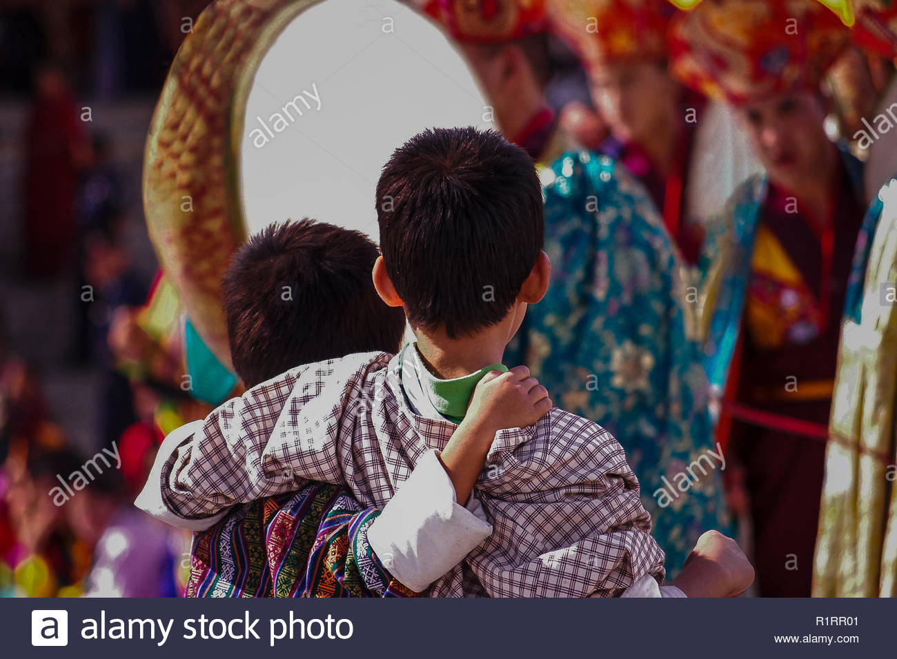 Two young boys in traditional costume watching the celebrations at the Thimphu Tsechu Festival, in Bhutan, Crowd scene, musicians, blurred background - Stock Image